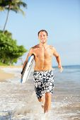 Beach lifestyle people - man surfer with surfing bodyboard running in water on tropical beach. Fit m