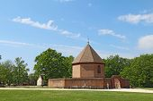 The Powder Magazine In Colonial Williamsburg, Virginia, Against A Bright Blue Sky