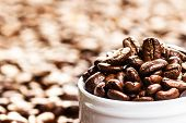 White Cup Full Of Roasted Coffee Beans On Heap Of Coffee Beans Background. Coffee Background Texture