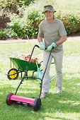 Full length portrait of a smiling man mowing the lawn