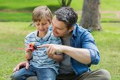 stock photo of aeroplane  - Young boy with toy aeroplane sitting on father - JPG
