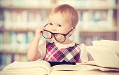 stock photo of clever  - Happy funny baby girl in glasses reading a book in a library - JPG