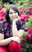 Beautiful Girl In Summer Garden Near Blooming Rosebush
