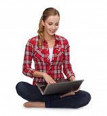 school, education, internet and technology concept - young girl sitting on the floor with laptop com