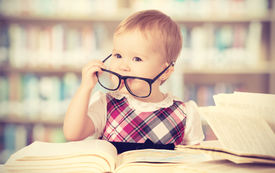 picture of schoolgirl  - Happy funny baby girl in glasses reading a book in a library - JPG