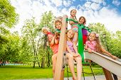 foto of chute  - Happy group of kids together on playground chute in the park during summer time - JPG