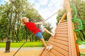 Positive boy climbs on wooden construction