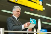 smiling senior businessman looking at his air ticket at airport
