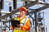 happy middle aged electrical engineer with clipboard in substation