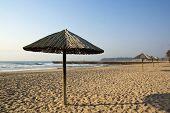 Sun Shade Umbrellas Lined Up On Empty Beach