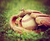 a baseball in an old glove on a grass background toned with a vintage retro instagram filter