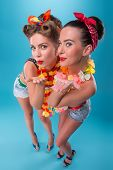 foto of hawaiian girl  - Top view portrait of two beautiful emotional coquette sexy girls with pretty smiles in pinup style with Hawaiian flowers necklaces - JPG