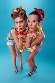 image of hawaiian girl  - Top view portrait of two beautiful emotional coquette sexy girls with pretty smiles in pinup style with Hawaiian flowers necklaces - JPG