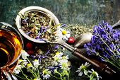 stock photo of black tea  - Herbal tea with wild flowers and berry on wooden background  - JPG
