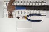Hammer and pliers on keyboard on office desk