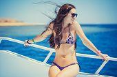 Young woman in bikini enjoying the viewon  yacht