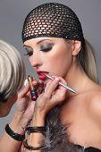 Beauty girl with makeup lip gloss and hairnet. Makeup artist applying lip gloss on face of woman.