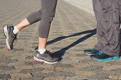 Couple in running shoes facing each other on a sunny day