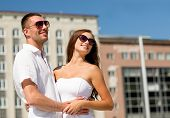 love, travel, tourism, people and friendship concept - smiling couple wearing sunglasses hugging in
