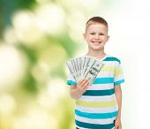 financial, planning, childhood and ecology concept - smiling boy holding dollar cash money in his ha
