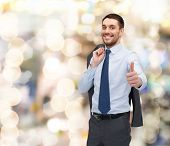business, gesture and people concept - smiling young and handsome businessman showing thumbs up