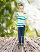 childhood, summer, gesture and people concept - smiling little boy showing thumbs up over plants and