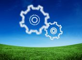 Cloud in shape of cogs and wheels against green field under blue sky