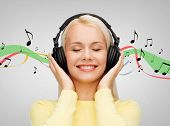 music and technology concept - smiling young woman with closed eyes listening to music with headphon