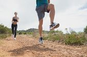 Low angle view of fit young couple running on countryside road