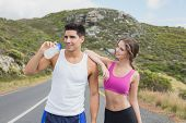 Portrait of a fit young couple standing on the open road together