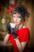 Fashionable attractive young woman in red dress drinking coffee in restaurant. Beautiful brunette