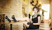 Fashionable attractive young woman in black dress sitting comfortable in restaurant. Beautiful girl