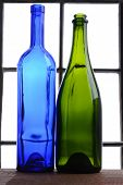 Empty wine bottle still life. A blue and a green wine bottle in front of a window.