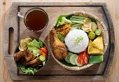 Famous traditional Indonesian food. Delicious nasi ayam penyet with sambal belacan. Fried chicken ri