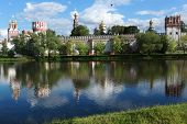 MOSCOW, RUSSIA - JUNE 4, 2012: People walks around the pond under the walls of Novodevichy Convent. Since 2004, the Convent is listed as UNESCO World Heritage site