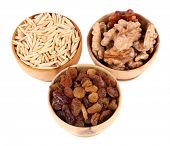 Small wooden bowls with raisins, walnuts and oats isolated on white