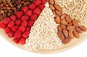Big round plate with raisins, raspberries, oatmeal, nuts and dried apricots divided on sectors on wh