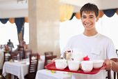 Young Smiling Affable Waiter Keeps Tray With Dishes At Restaurant, Wide Angle
