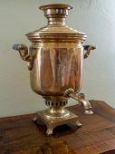 Old Russian tea brewing samovar standing on wooden tea table