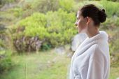 Side view of a young woman wearing bathrobe against blurred plants