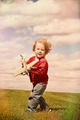 Young boy running with a toy airplane