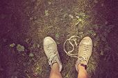 Dirty sneakers on a weedy lawn. Instagram effect