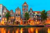 stock photo of old boat  - Night city view of Amsterdam canal Herengracht with typical dutch houses boats and bicycles Holland Netherlands - JPG