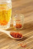 image of saffron  - Spoon dry saffron on a background a glass with the infusion of saffron - JPG