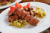Adana kofte with vegetables and Aleppo pepper