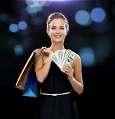 shopping, sale, gifts, money and holidays concept - smiling woman in dress with shopping bags and mo