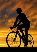 silhouette of the cyclist riding a road bike at sunset