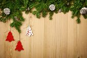 Christmas background with fresh fir tree, decorative handmade trees and cones on wood