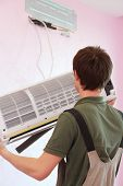 Young worker installs air conditioning in the new apartment