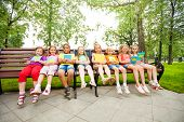 Children sitting in a row on bench with notebooks